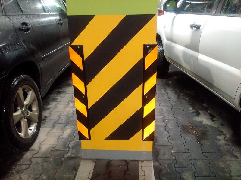 kolorowe zdjecie przedstawia filar betonowy, a na którym zamontowane zostały narożnikowe ochraniacze ścian w kolorze czarno-żółtym w pasy