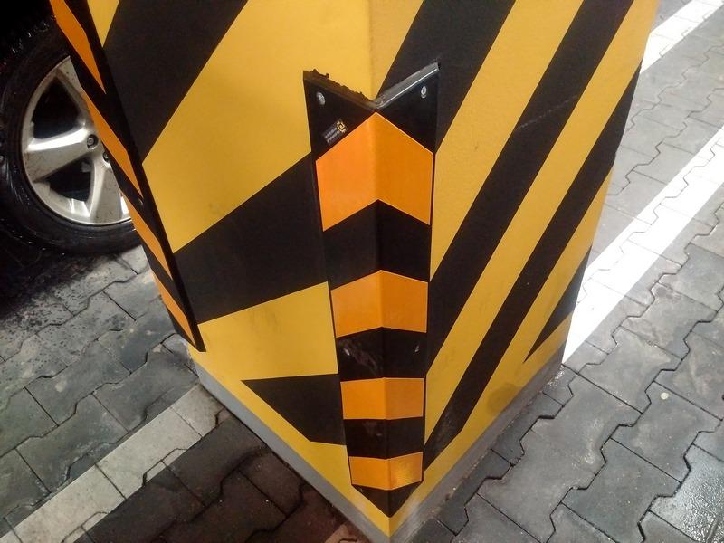 zdjęcie betonowego filara przedstawia zamontowany ochraniacz narożny w czarno-żółte pasy