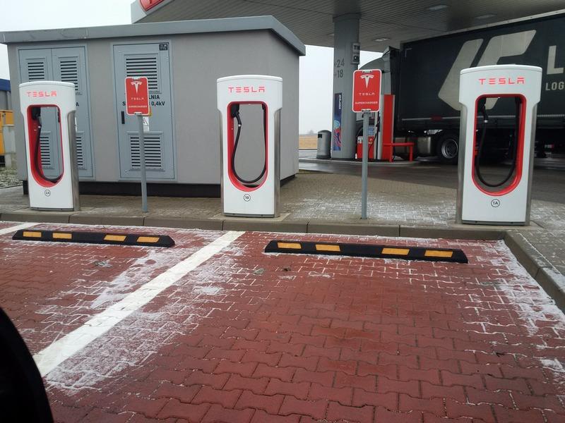 parking ze stanowiskami ładowania tesla. na parkingach zainstalowane są ograniczniki parkowania.